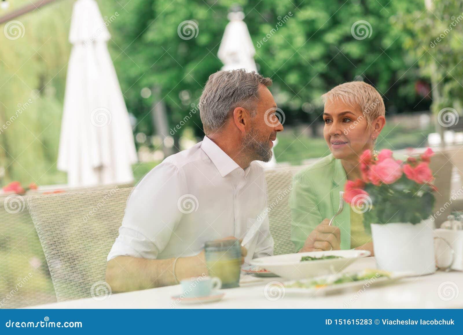 Couple of mature husband and wife enjoying breakfast outside