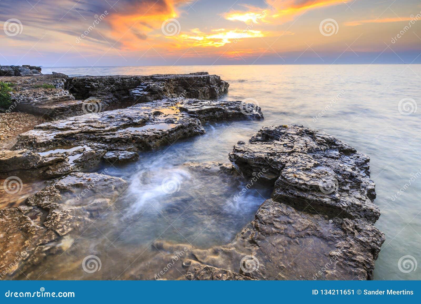 Enjoying the colorful sunset on a beach with rocks on the Adriatic Sea coast Istria Croatia