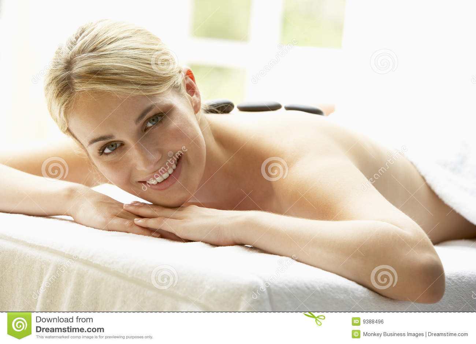 Enjoying hot stone treatment woman young