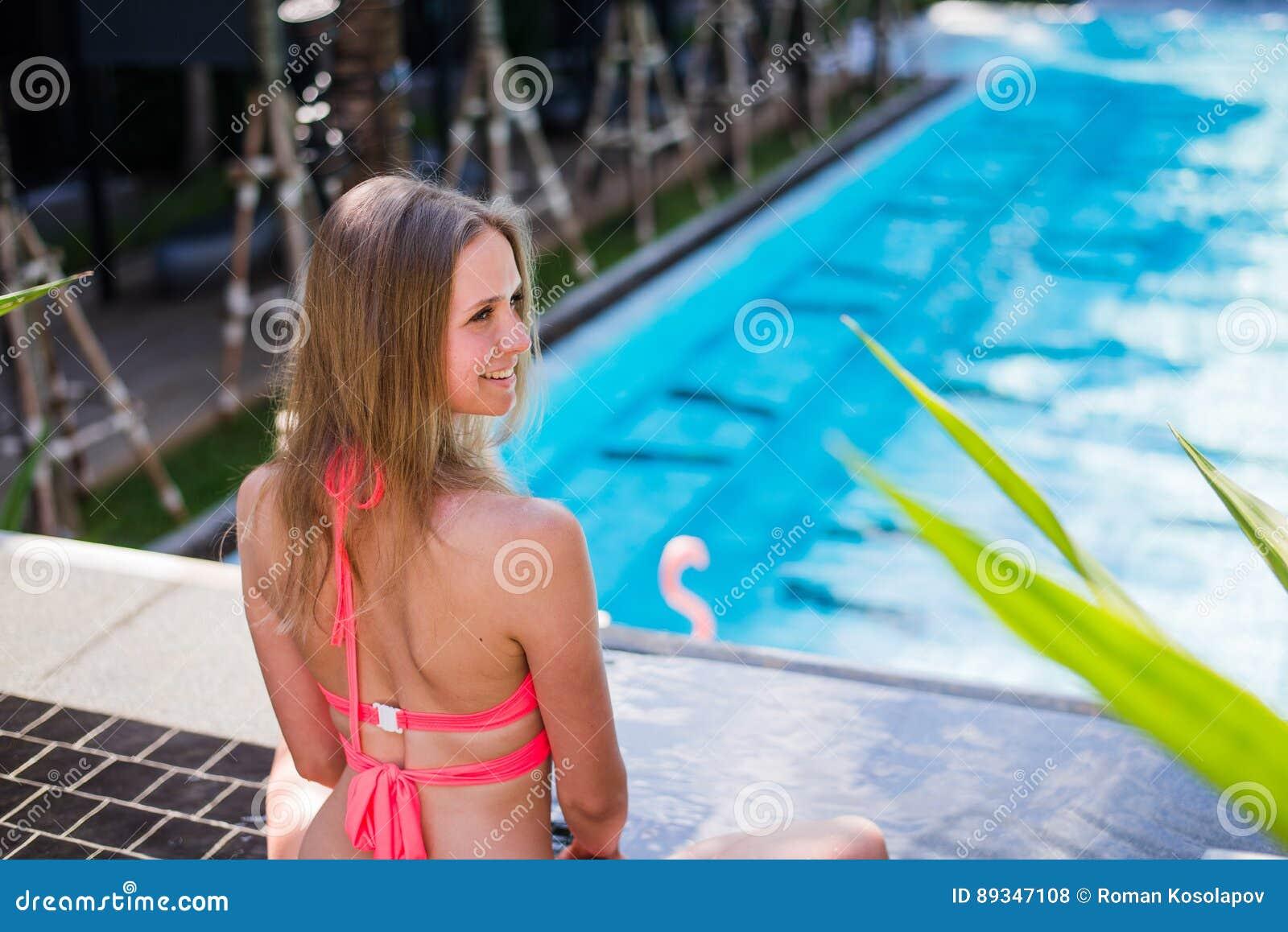d5be5c2c73b Enjoying Suntan. Pretty Young Woman In Bikini Sitting Near Swimming ...