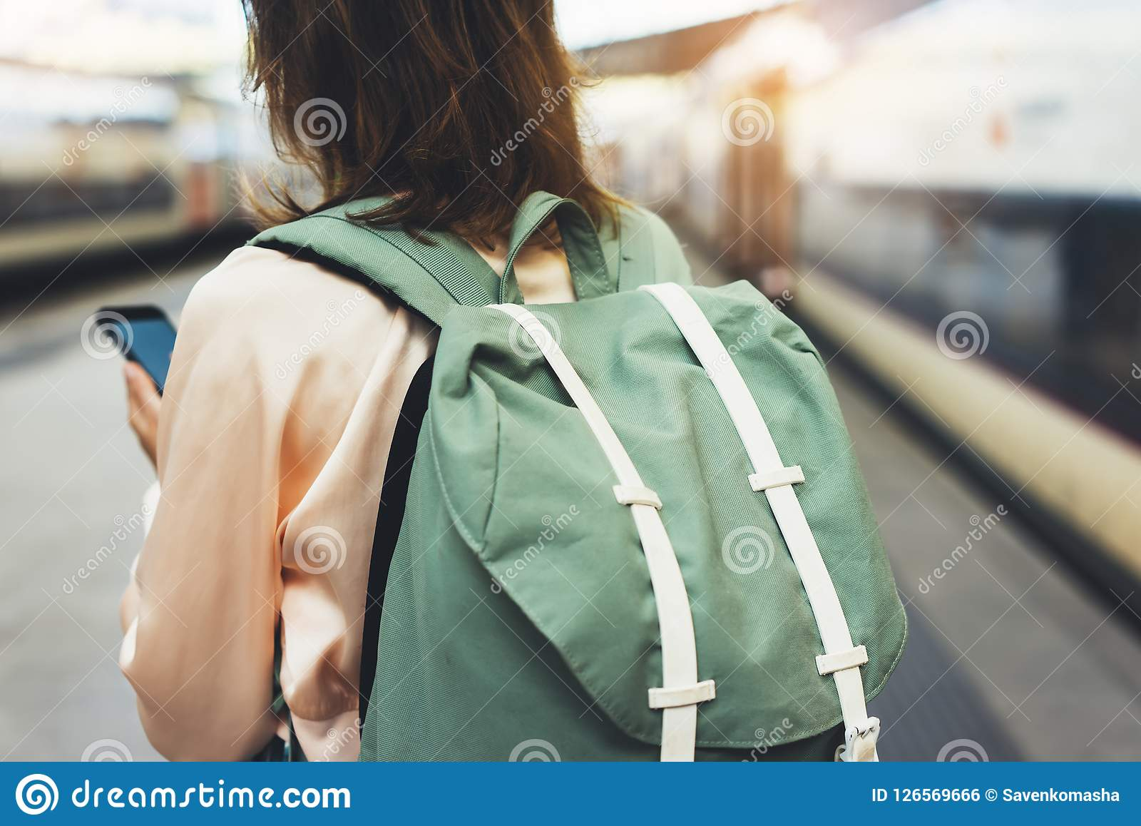 Enjoying travel. Young hipster woman waiting on the station platform with backpack on background electric train using smartphone