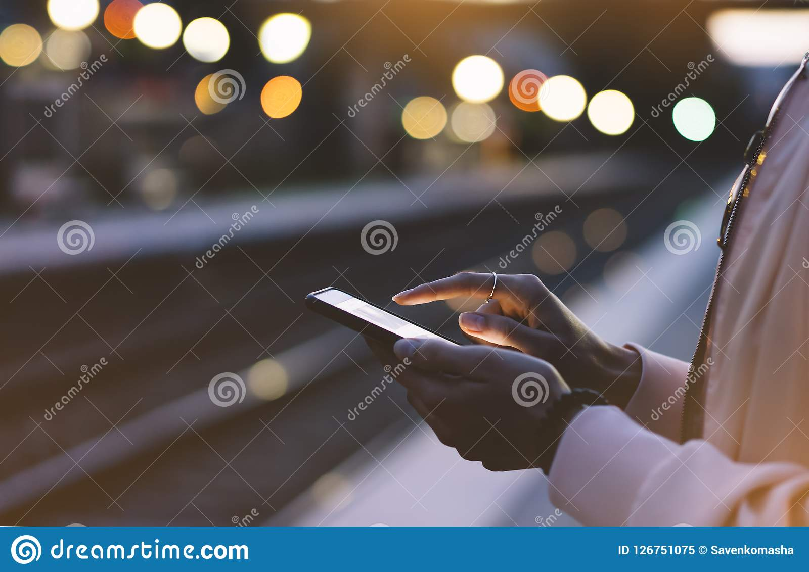 Enjoying travel. Young woman waiting on station platform on background light electric moving train using smart phone in night