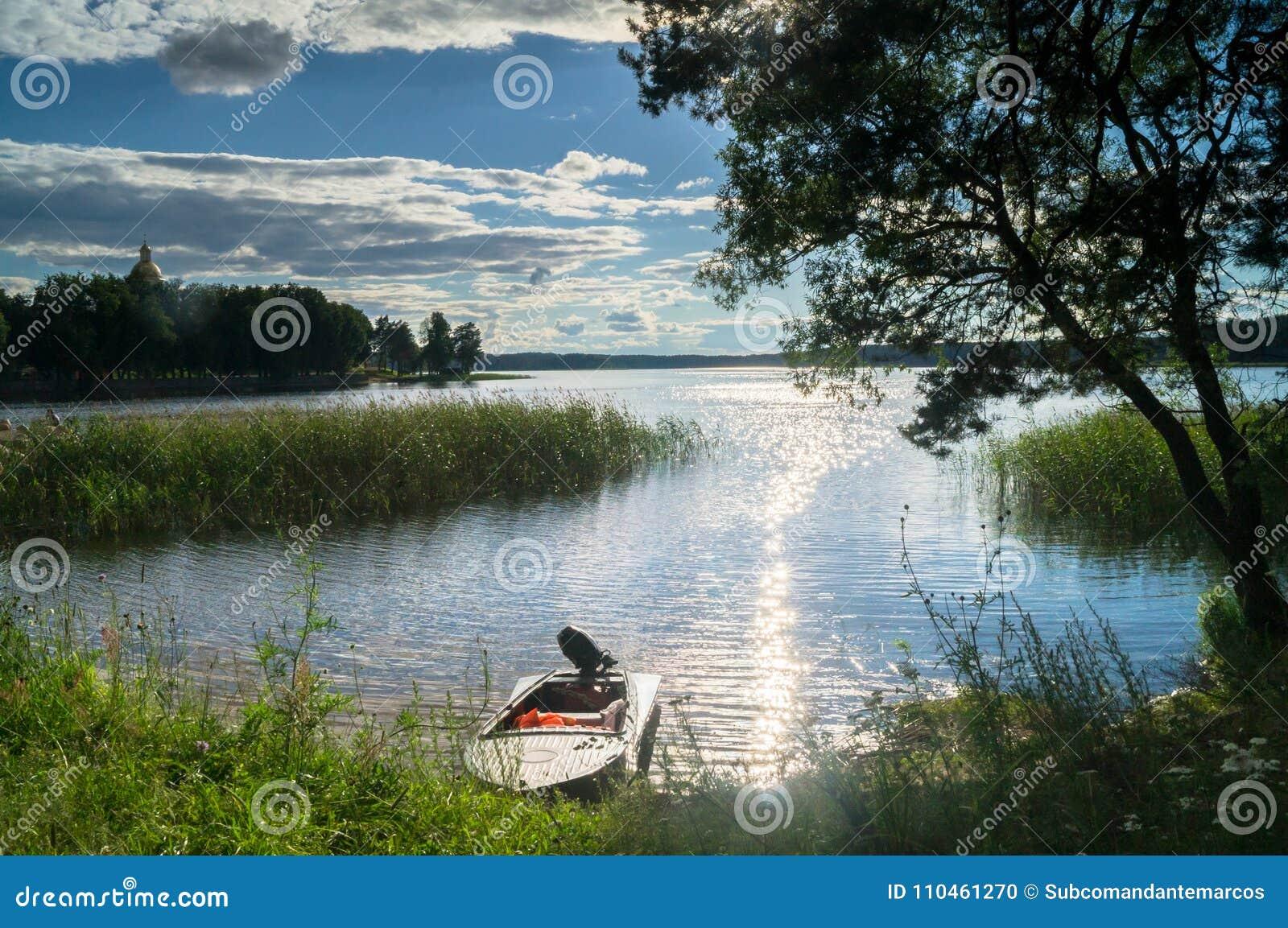 Enkel fishers`-motorbåt som förtöjas till den strand- skogen av sjön Seliger under det bländande solljuset, Ryssland