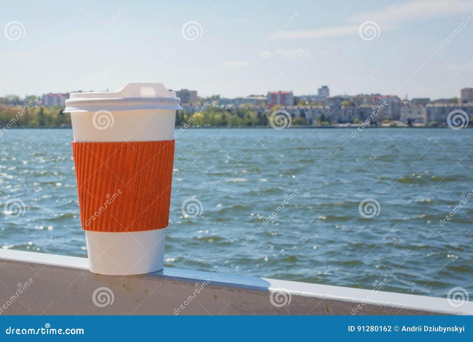 Enkel kopp för kaffe på bakgrunden av sjön och staden i bokeh