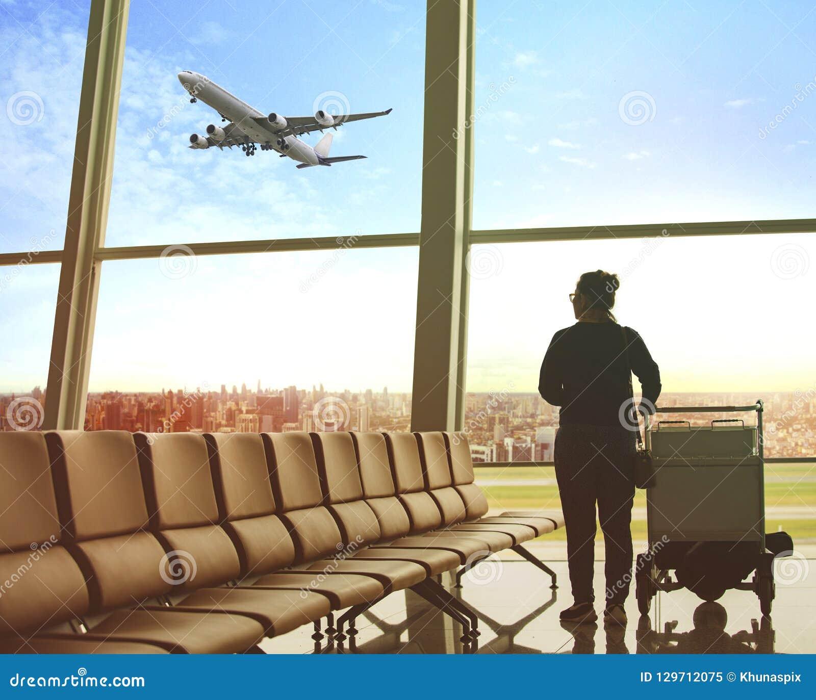 Enkel kvinna som sitter i fluga för flygplatsterminal och för passagerarenivå