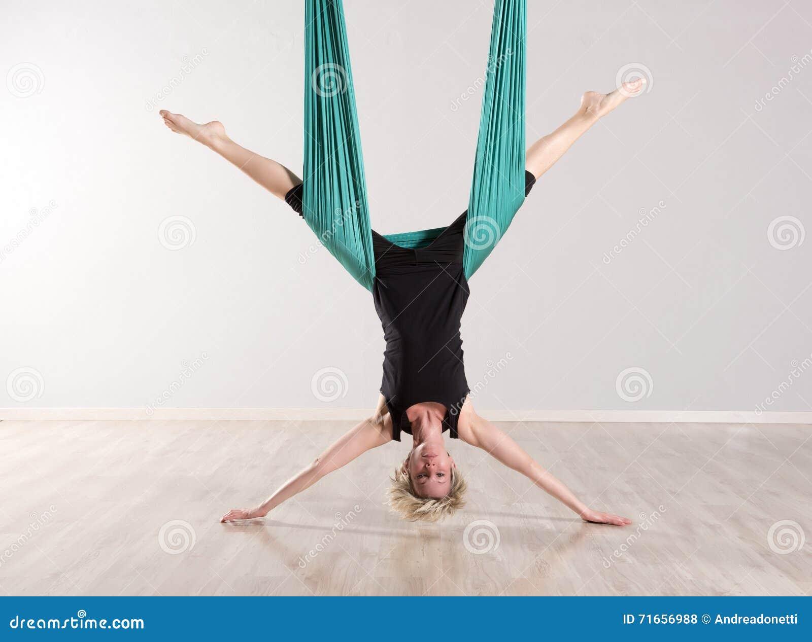Enkel uppochnervänd kvinna som gör flyg- yogasplittringar