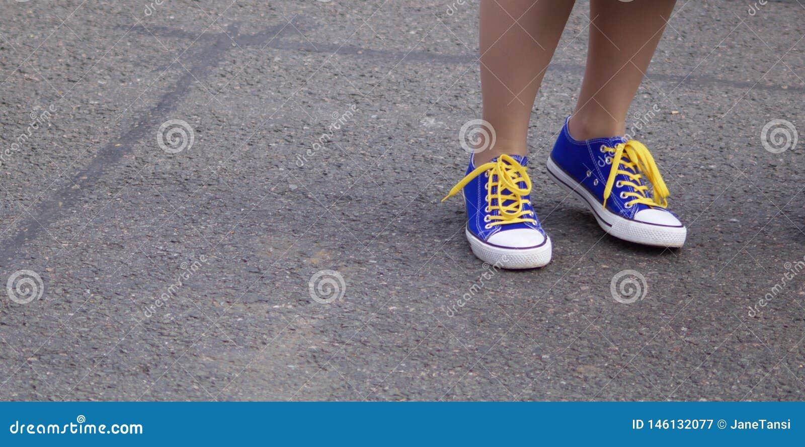Enkels die van meisje blauwe sportenschoenen met geel kant dragen tegen grijze bestratingsachtergrondafbeelding