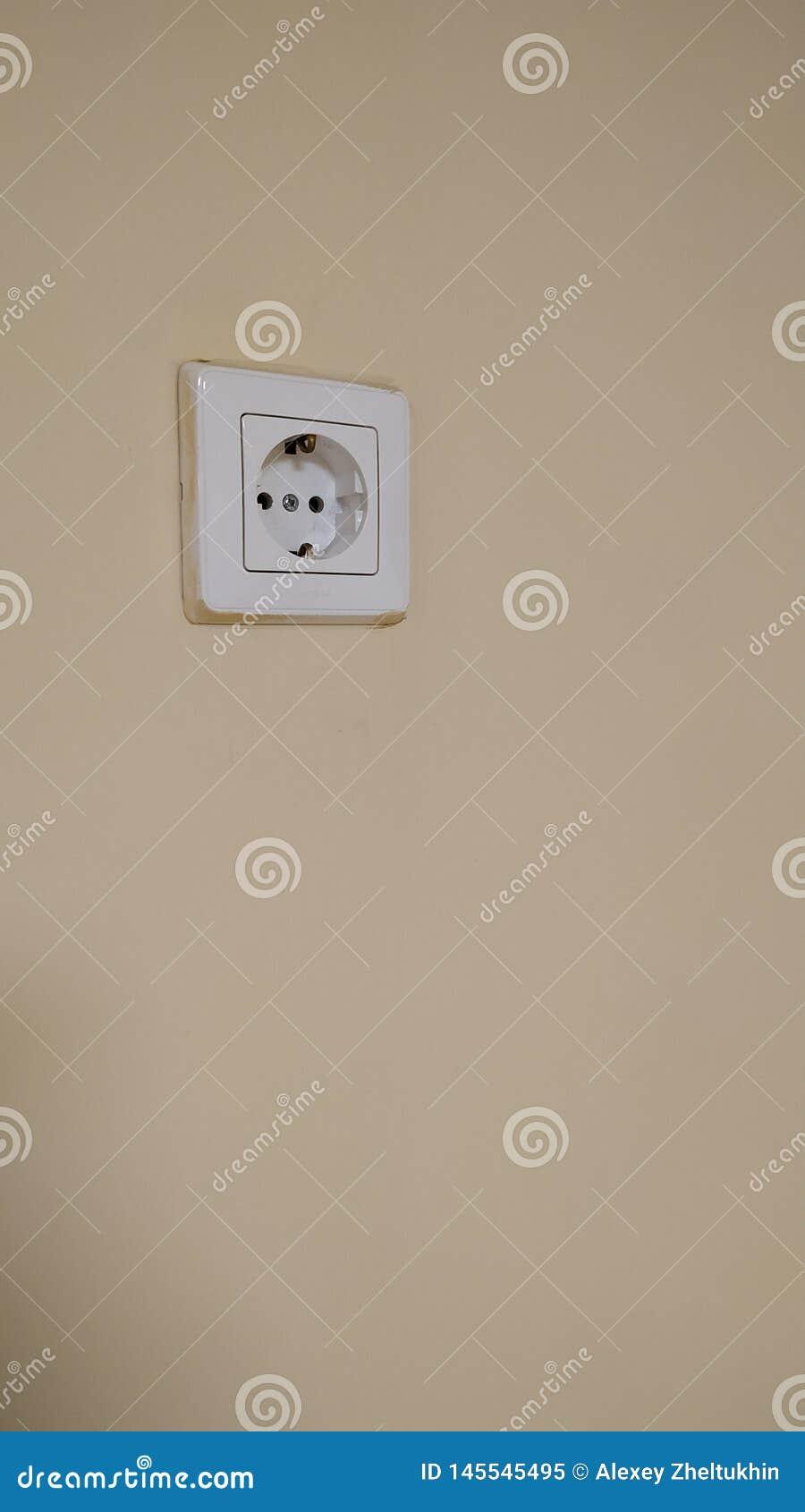 Enkelt elektriskt uttag på väggen som målas i beige färg N?rbild
