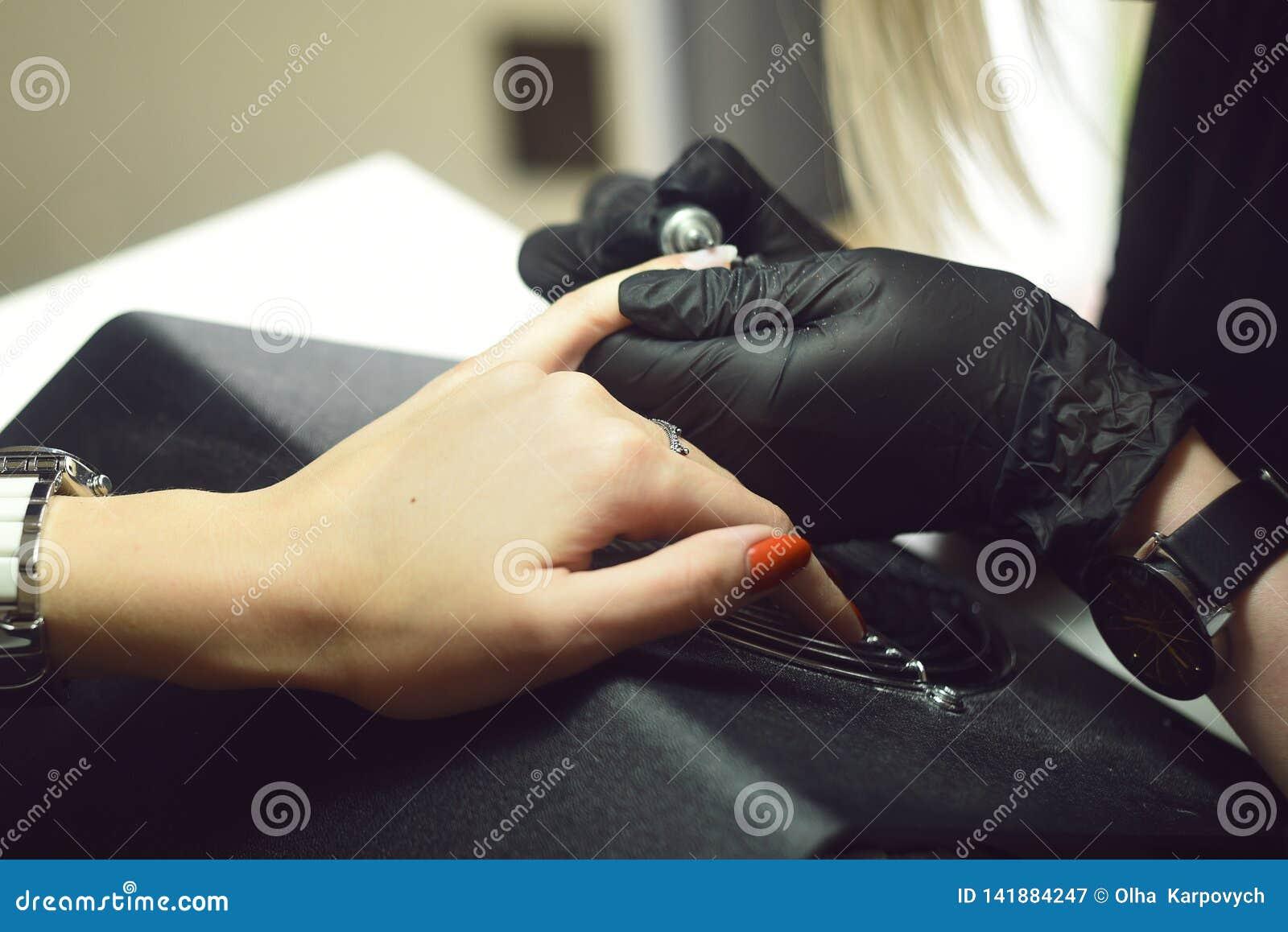 Enlèvement de gomme laque Le maître fait une manucure Jour de détente au salon de beauté Le maître de manucure fait la manucure s