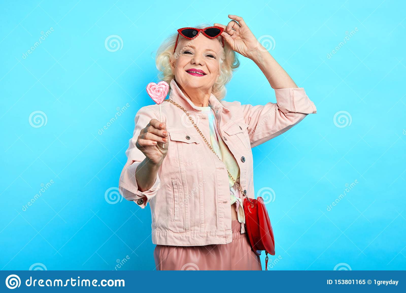 Enorm blond hög dam för glamour som av tar solglasögon, medan äta klubban