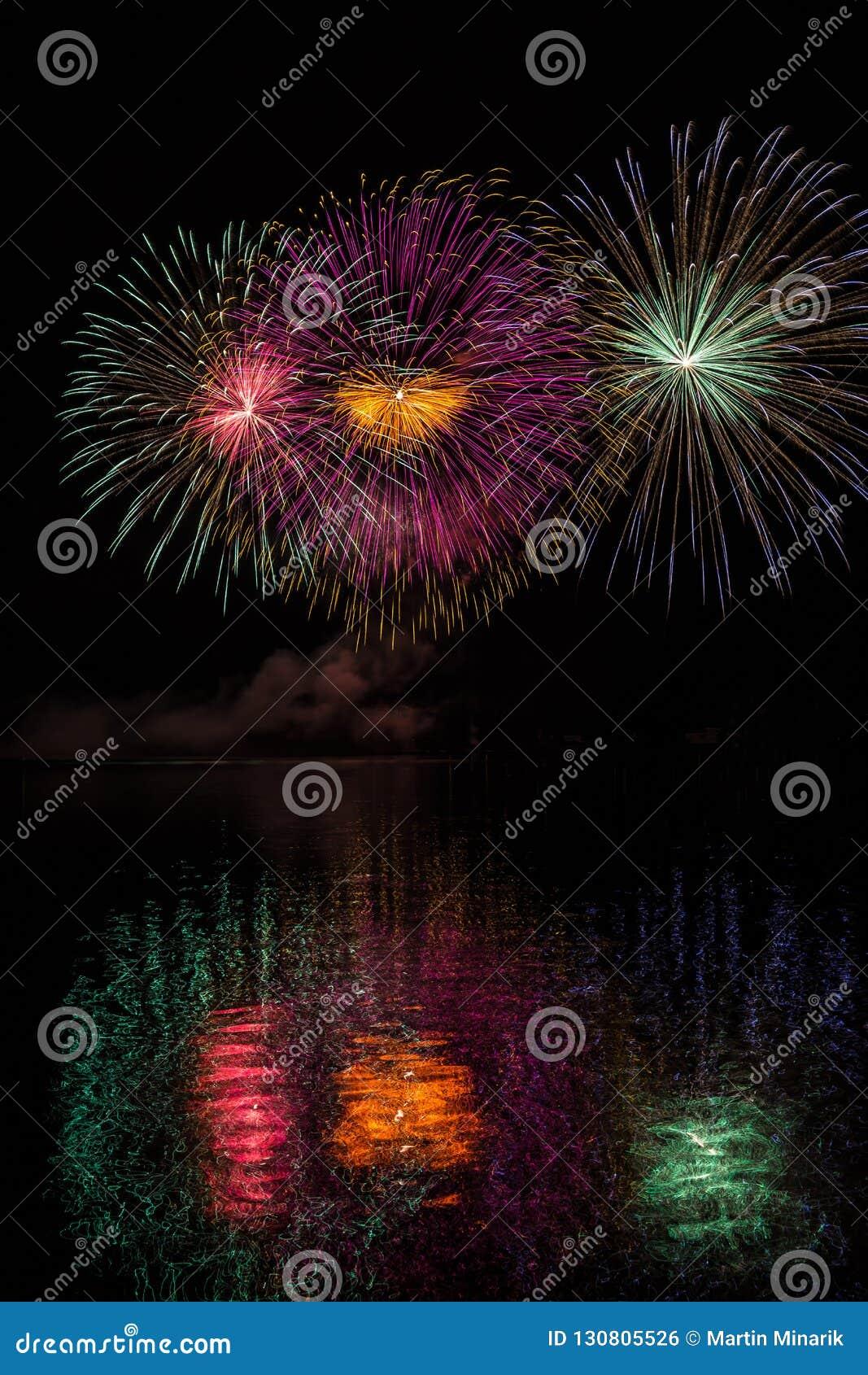 Enorme Mehrfarbensterne in den Feuerwerken über Oberfläche von Brnos Verdammung mit Seereflexion