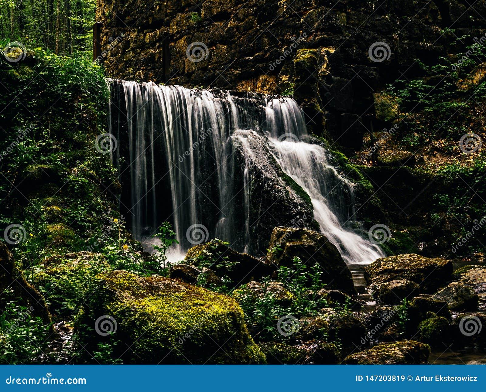 Enormer Wasserfall an den Ruinen einer alten Mühle im Wald