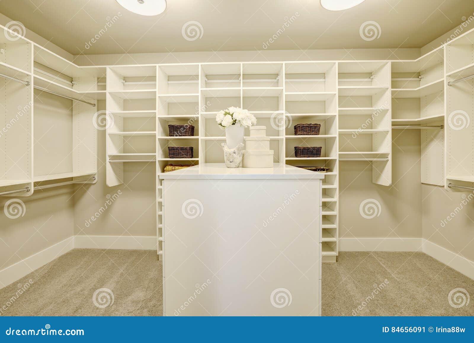 Enormt gå-i garderoben med hyllor, enheter och skokuggar