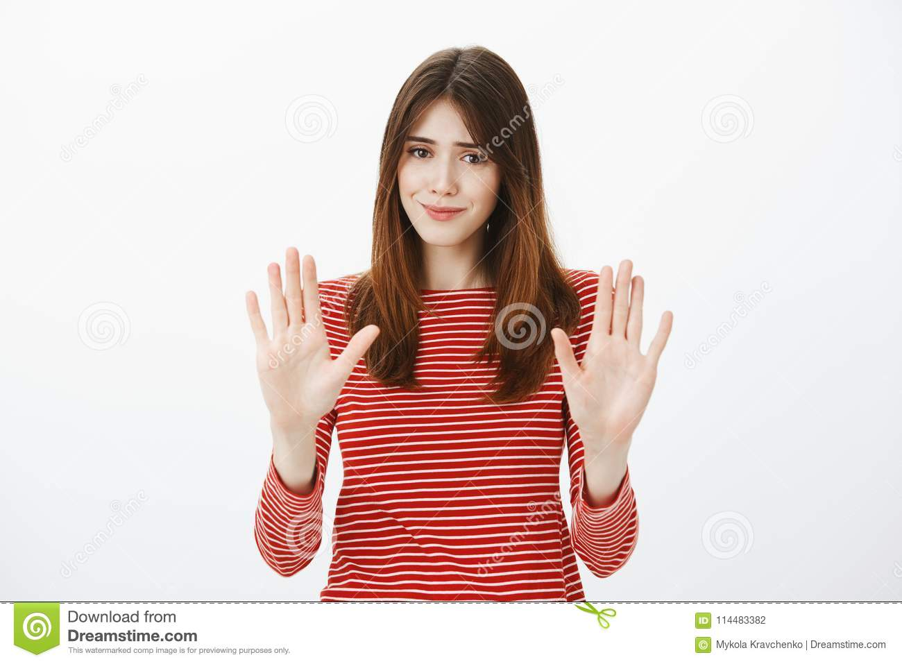 That is enough, thanks. Portrait of uncomfortable pretty brunette, raising palms in no or stop gesture, smiling