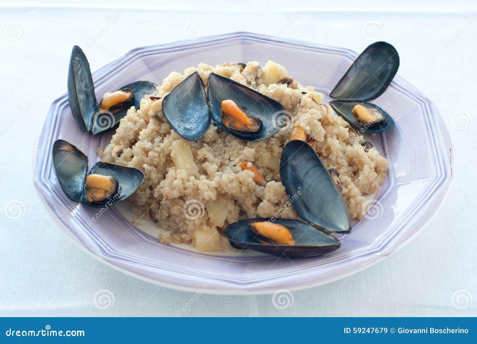 Ensalada caliente de la quinoa con los mejillones, los tomates y las patatas