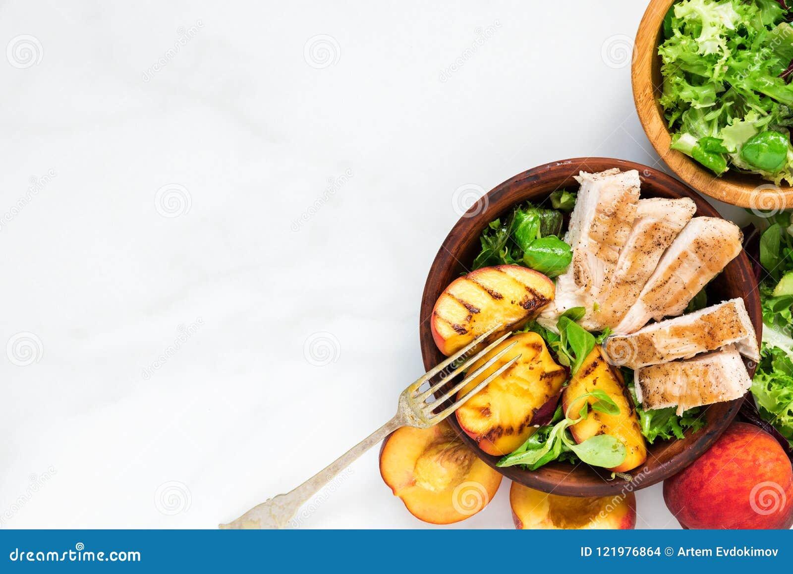 Ensalada con el pollo asado a la parrilla y melocotón en un cuenco con la bifurcación Alimento sano Visión superior