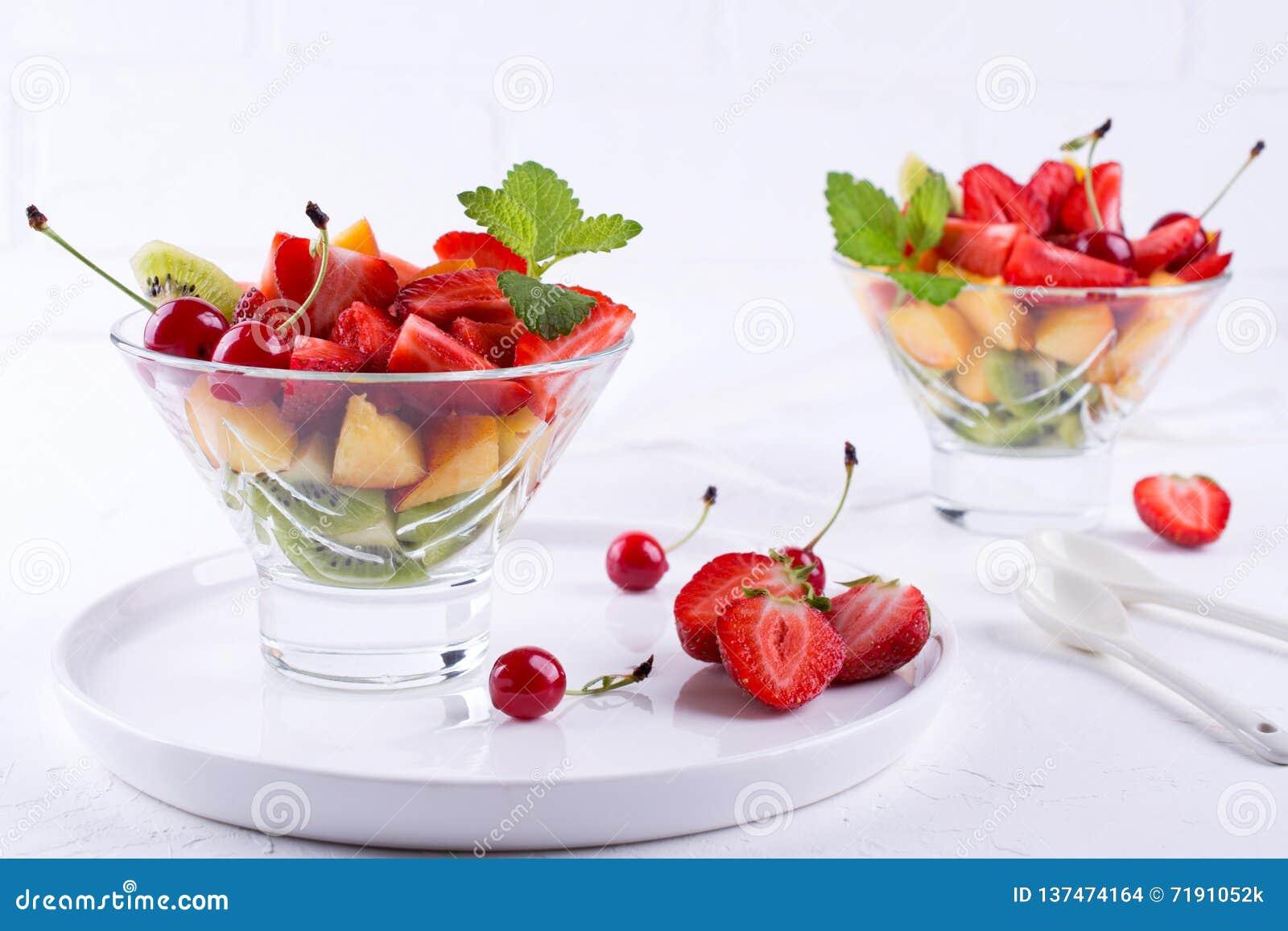 Ensalada de fruta colorida en el bol de vidrio Fresas, kiwis y postre de los albaricoques