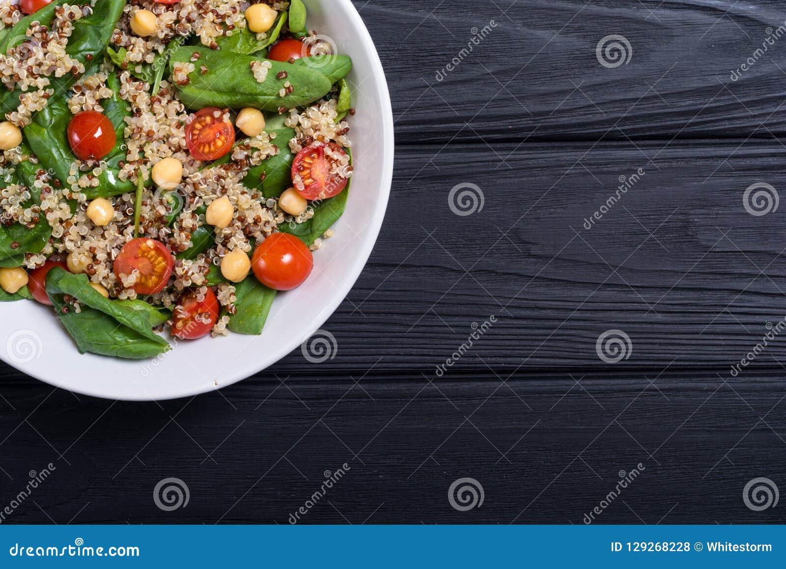 Ensalada de la espinaca con la quinoa, los tomates y el garbanzo