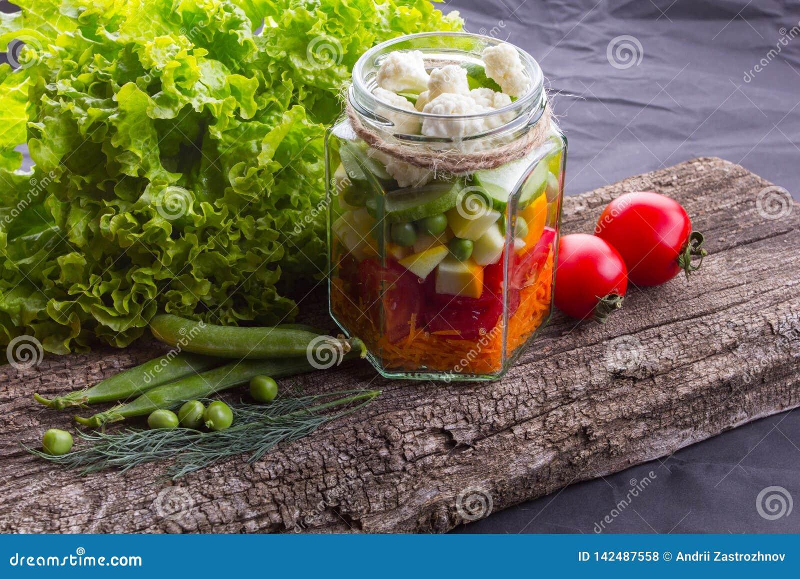 Ensalada de las verduras frescas con las hierbas en un tablero de madera, fondo texturizado negro