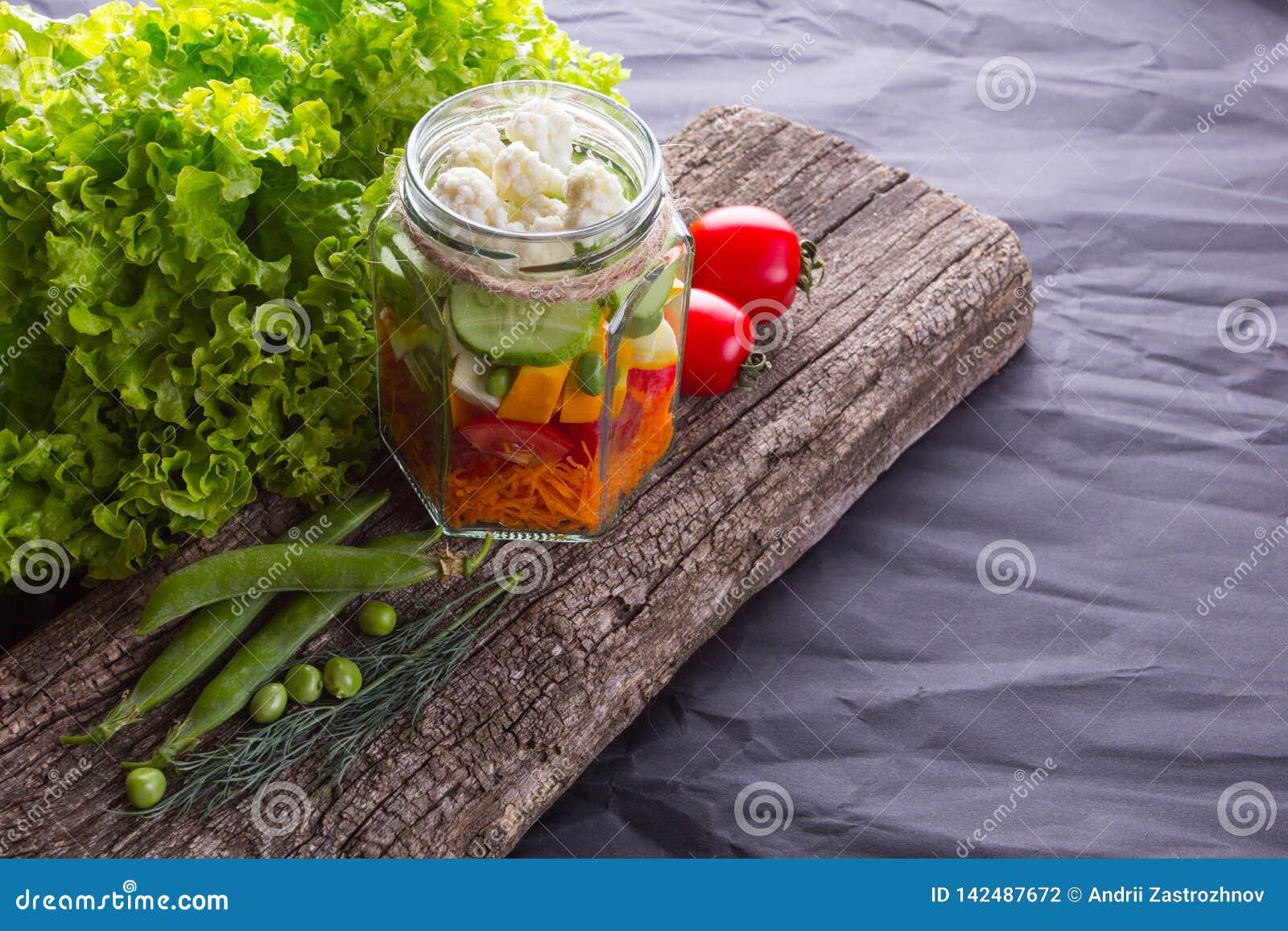 Ensalada de las verduras frescas con las hierbas en un tablero de madera