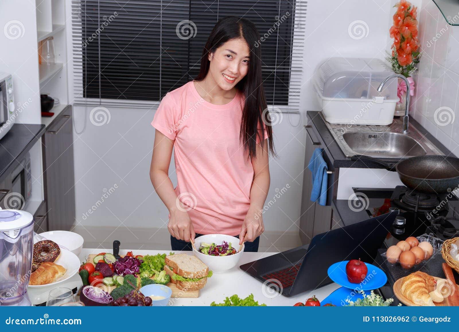 Ensalada de mezcla de la mujer mientras que cocina con el ordenador portátil en cocina