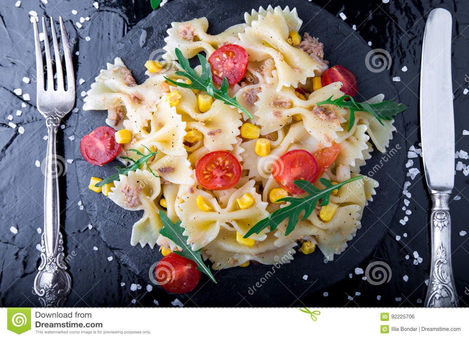 Ensalada de pasta en placa de la pizarra con los tomates cereza, atún, maíz y arugula cerca del cuchillo y de la cuchara Visión s