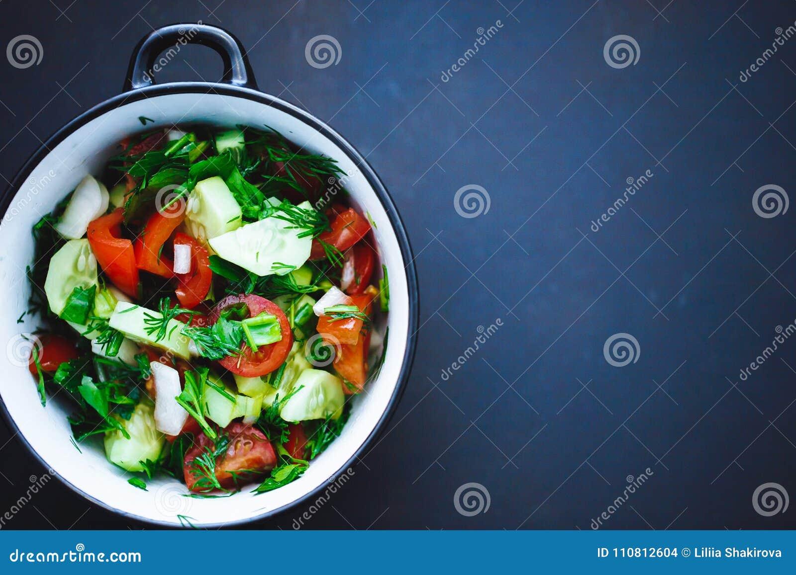 Ensalada de verduras frescas en una placa en un fondo negro, tomates, pepinos, eneldo, perejil, cebolla del verano Ciérrese para