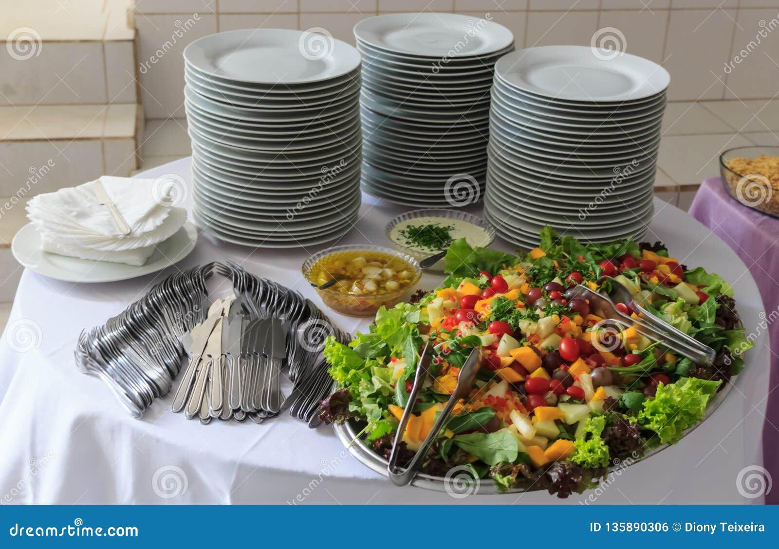 Ensalada deliciosa de verduras y de frutas Lechuga, tomate, perejil, arugula, uva, mango, melón En la tabla una pila de placas,