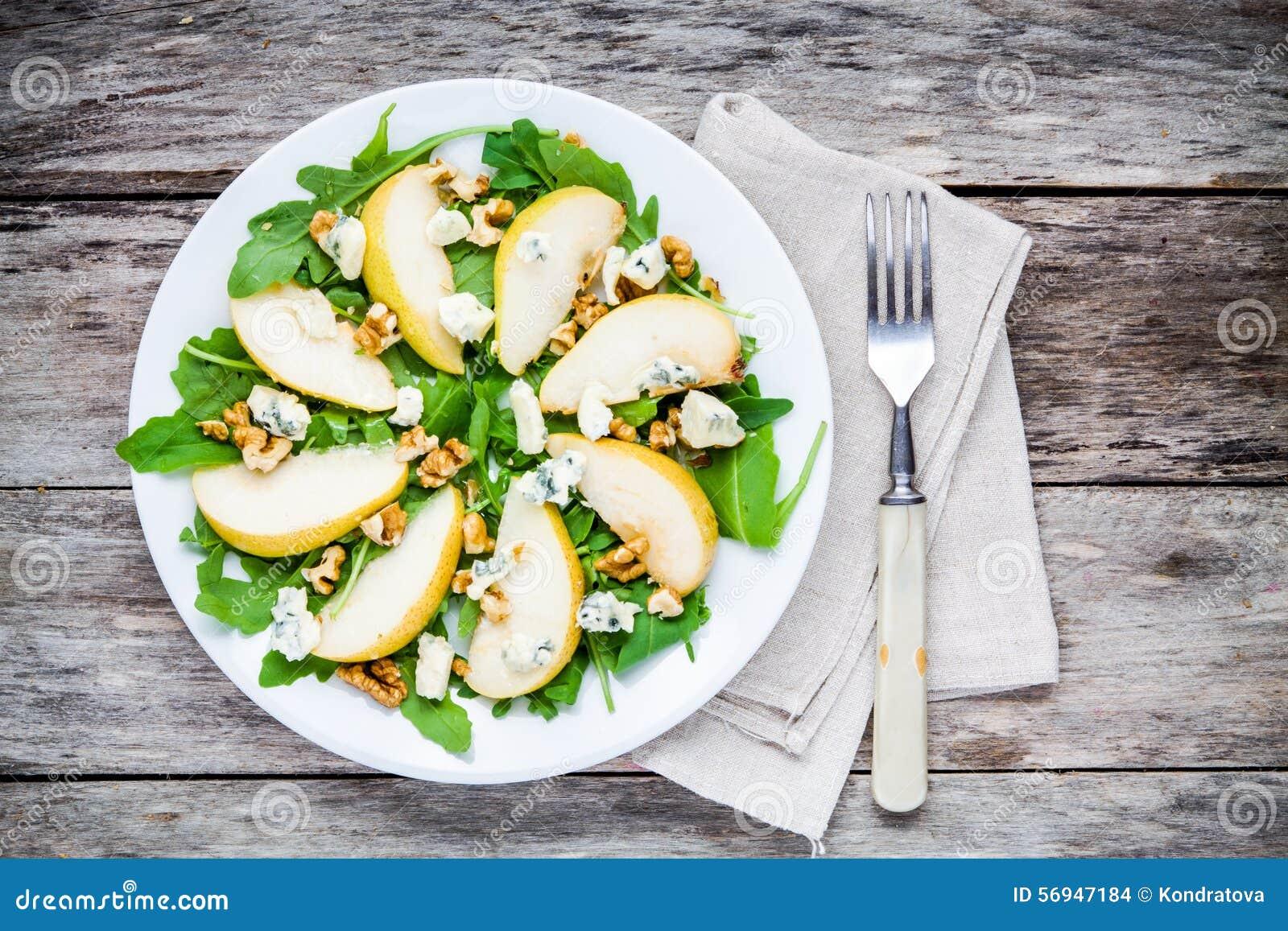 Ensalada fresca con arugula, la pera, las nueces y el queso verde