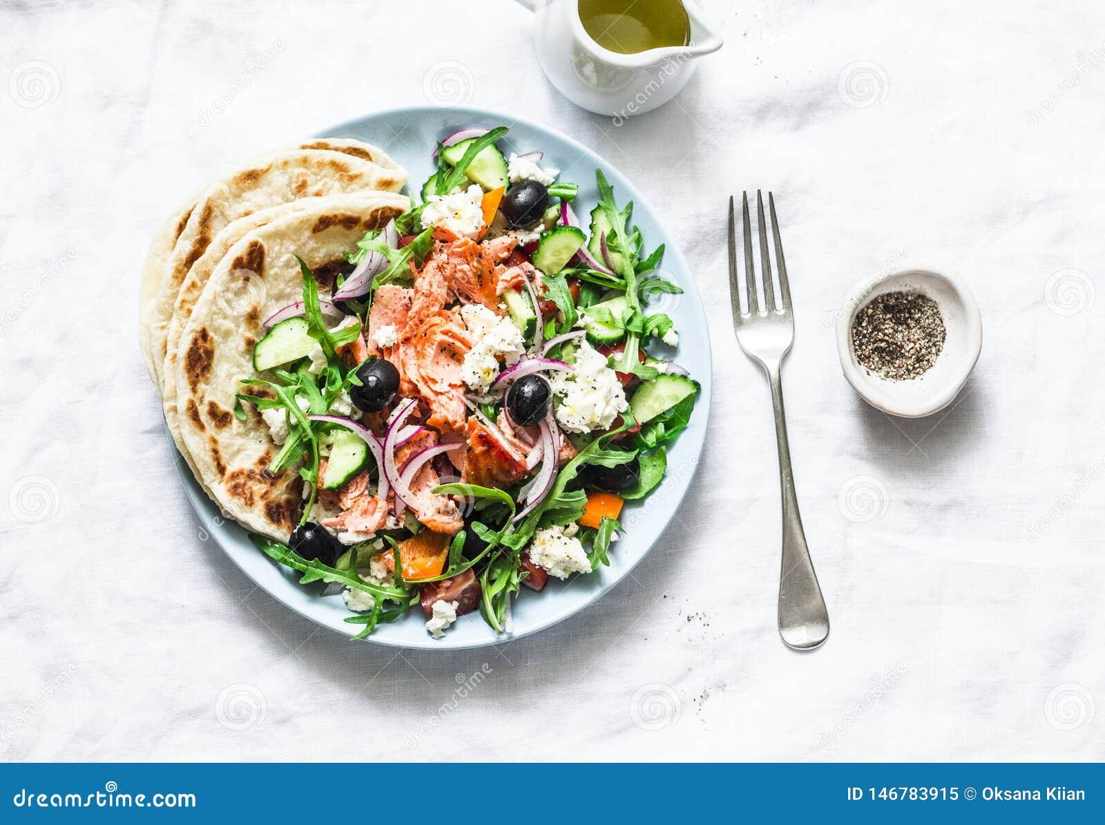 Ensalada griega con los salmones cocidos en un fondo ligero, visión superior Comida mediterr?nea sana de la dieta