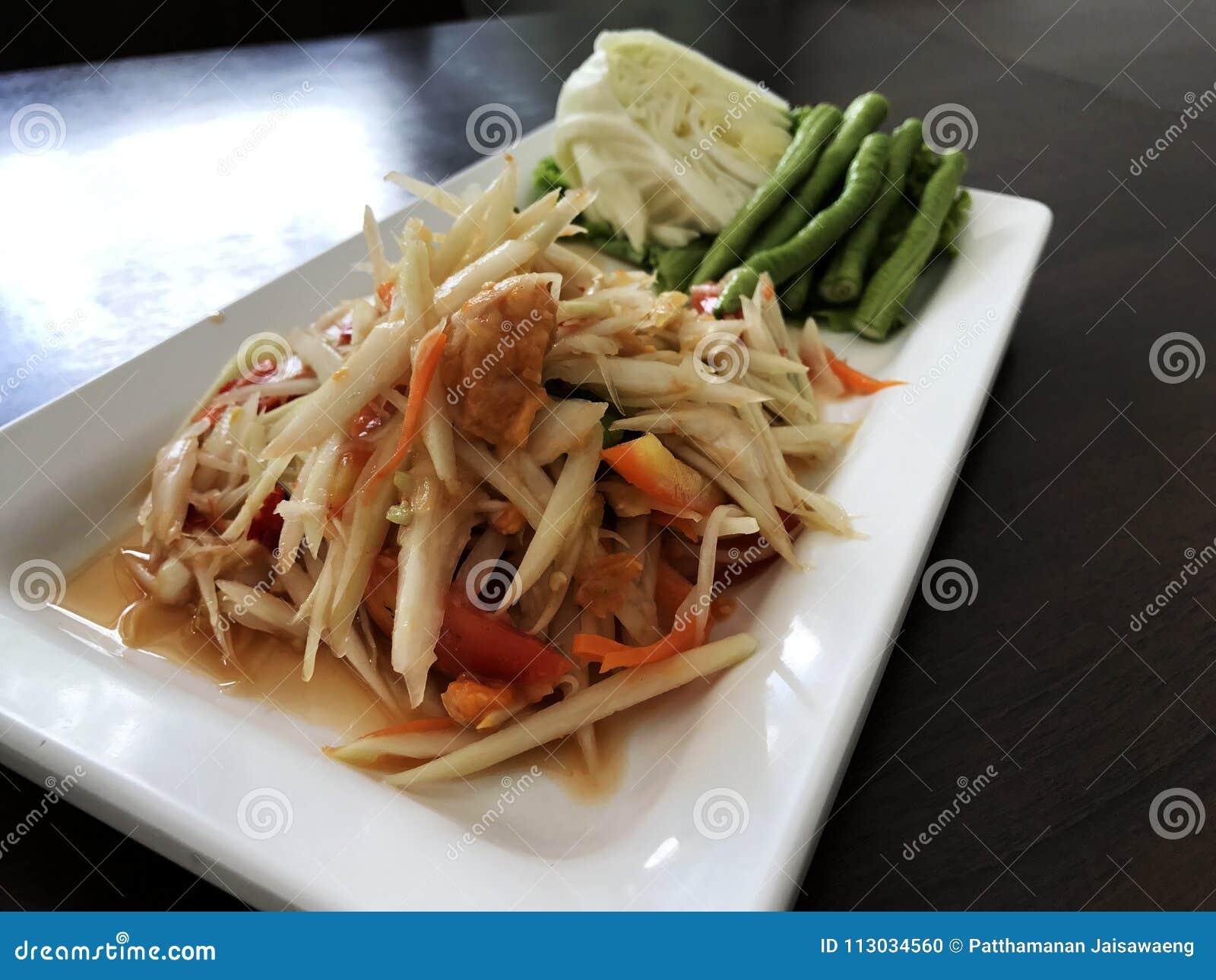 Ensalada picante de la papaya con la verdura en la tabla de madera Tradicional tailandés