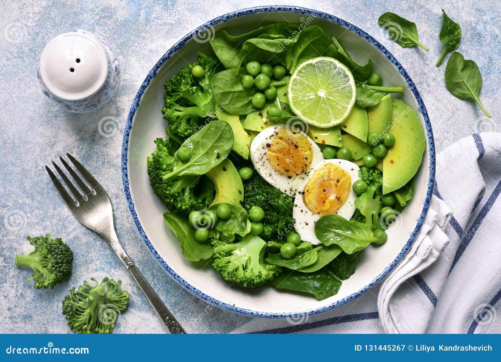 Ensalada vegetal verde con el aguacate, el bróculi, el guisante y los huevos hervidos en un fondo azul claro de la pizarra, de pi