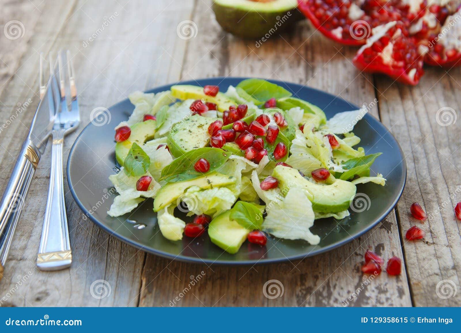 Ensalada vegetariana con el aguacate, verdes, las hojas, la granada y las hojas del letuce Tabla rústica de madera