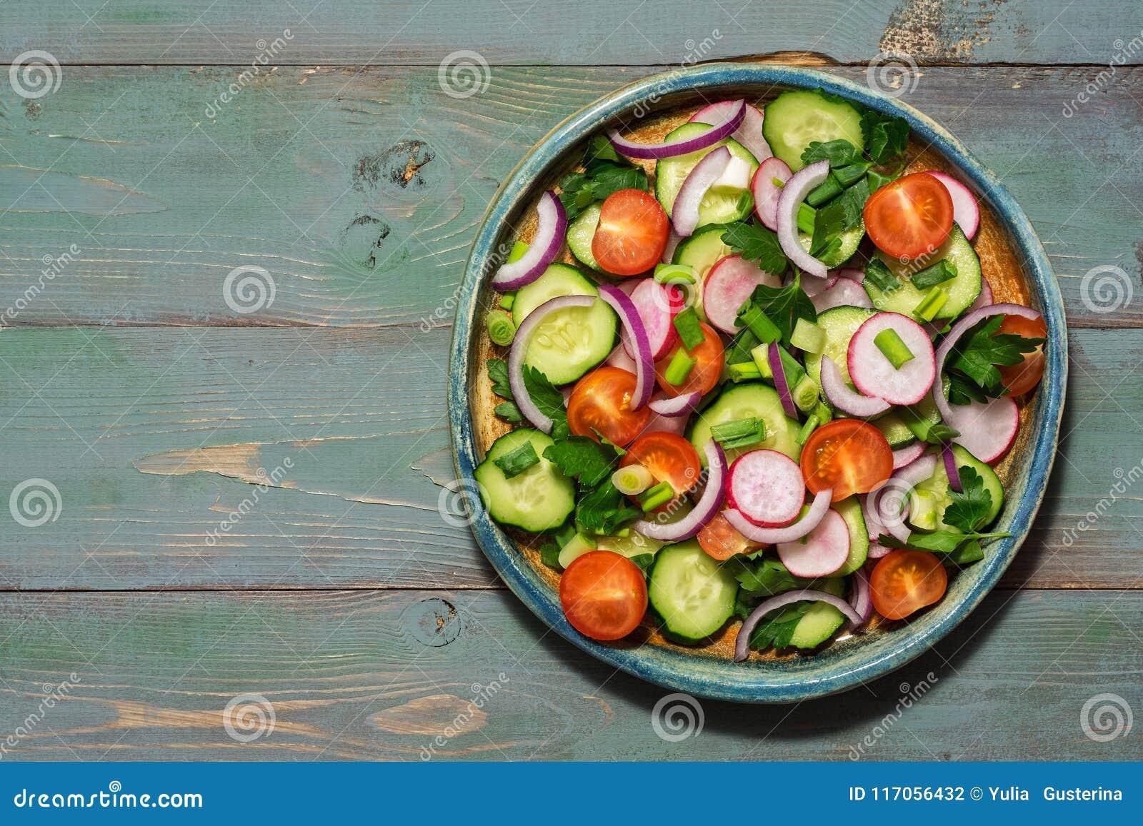 Ensalada vegetariana de verduras frescas en un fondo de madera verde Visión superior, espacio de la copia