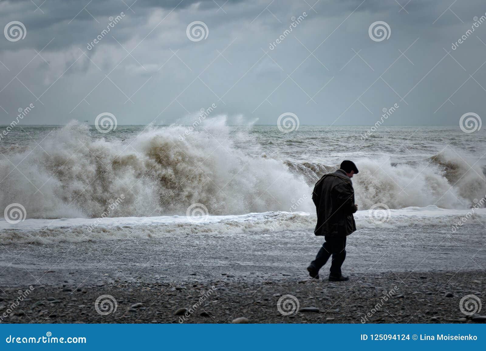 Ensam gamal man som promenerar kusten, baksidasikt