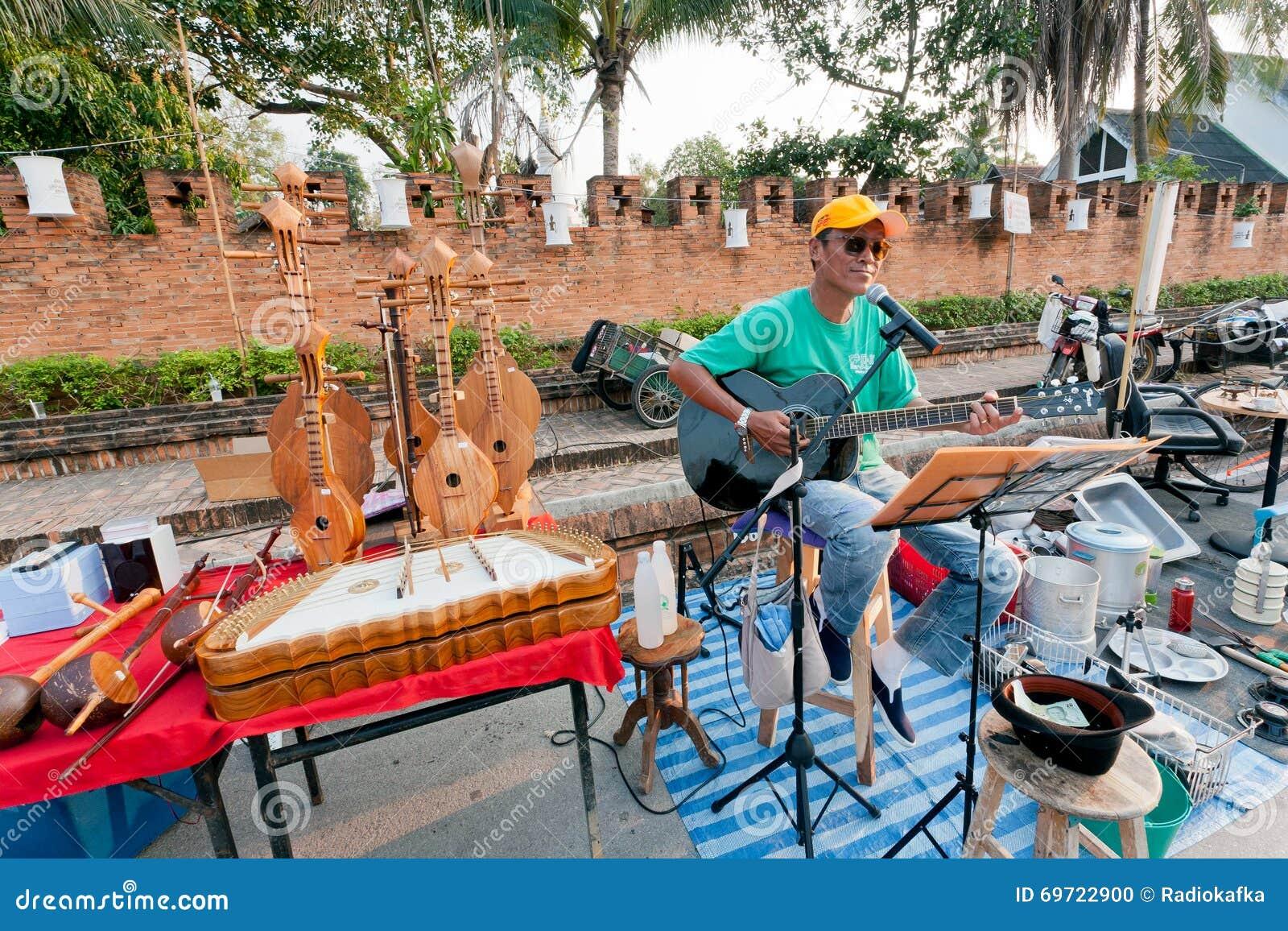 Ensam gitarrist som spelar musik på gatamässan som omges av musikinstrument