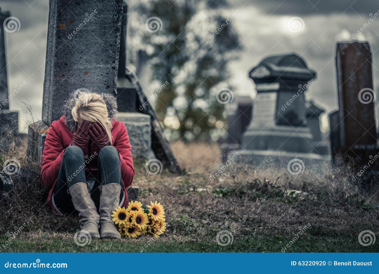 Ensam ledsen ung kvinna, i att sörja framme av en gravsten