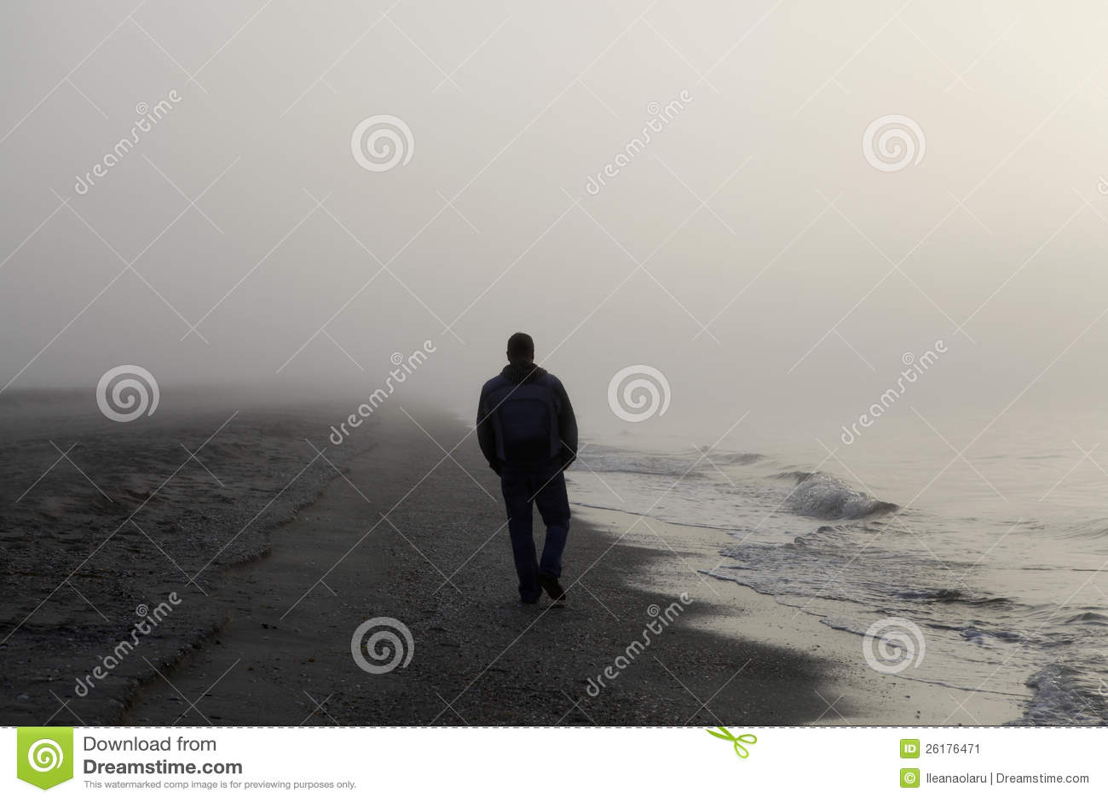 Ensam man som går på en strand