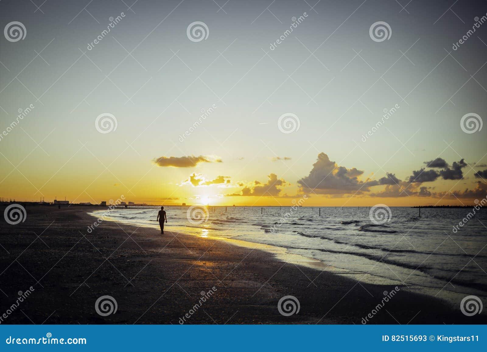 Ensam man som går på stranden på solnedgången