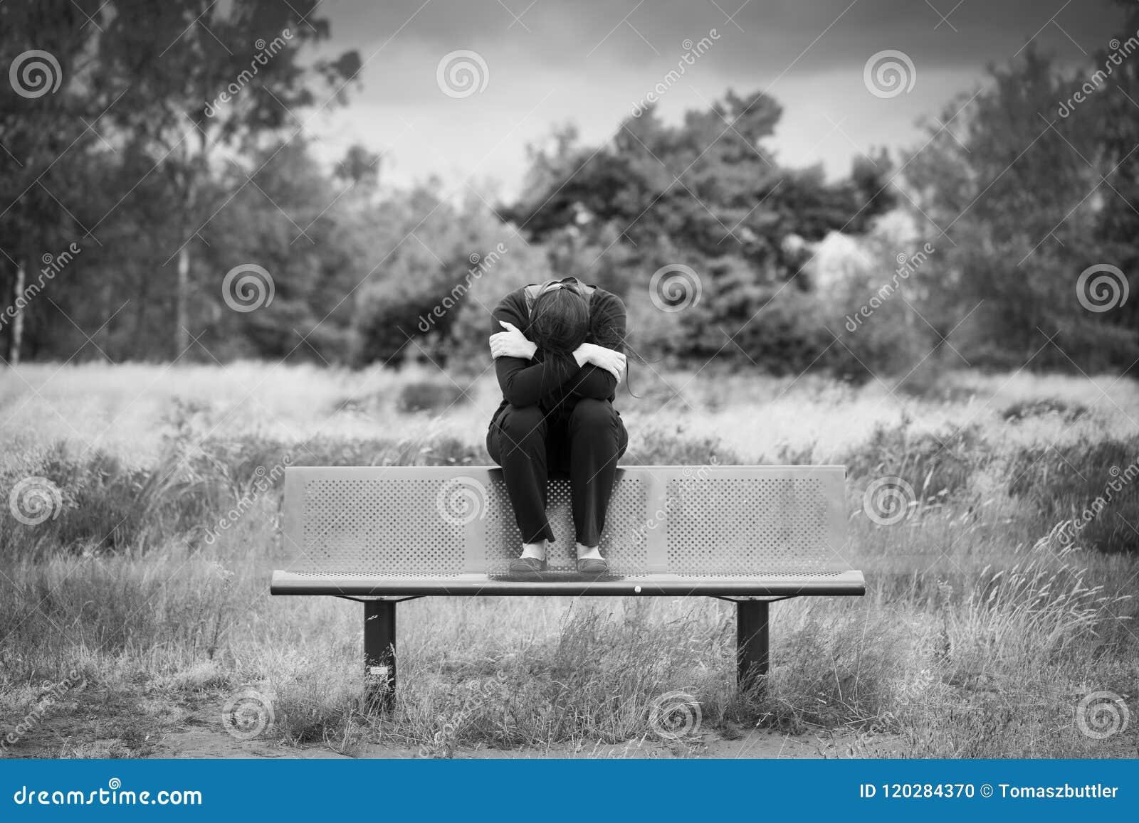 Ensamt ungt deprimerat ledset kvinnasammanträde på en bänk med armar korsade framme av hennes framsida monokrom stående
