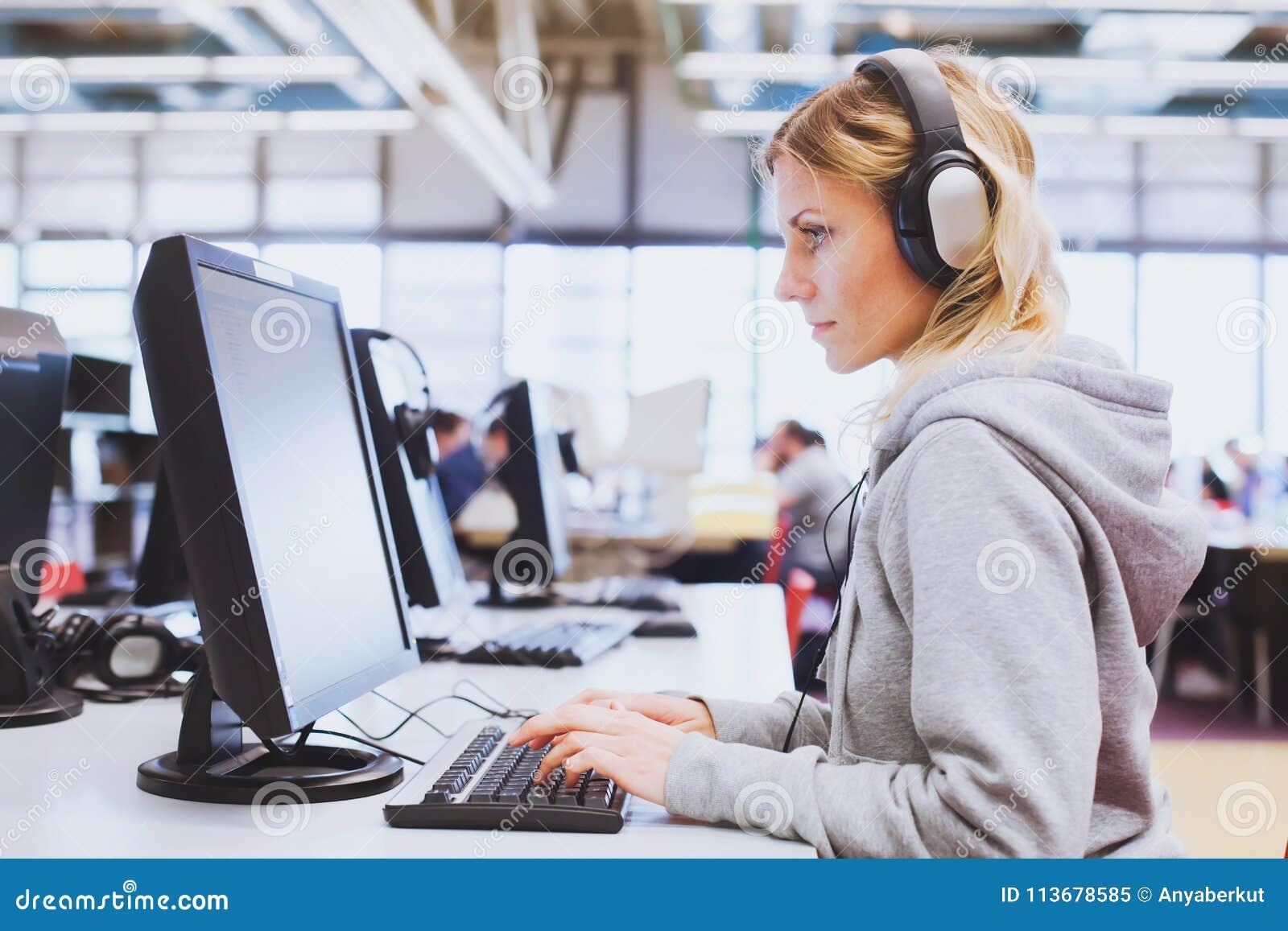 Enseñanza para adultos, estudiante en los auriculares que trabajan en el ordenador en la biblioteca