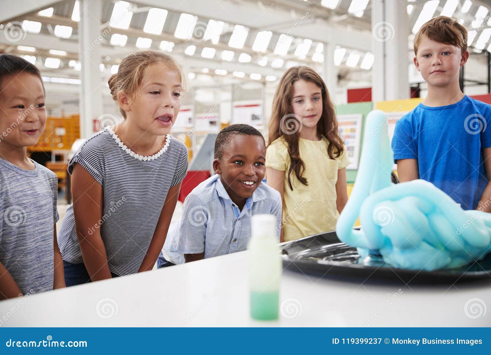 Enseñe a los niños que miran el experimento en el centro de la ciencia, cierre para arriba