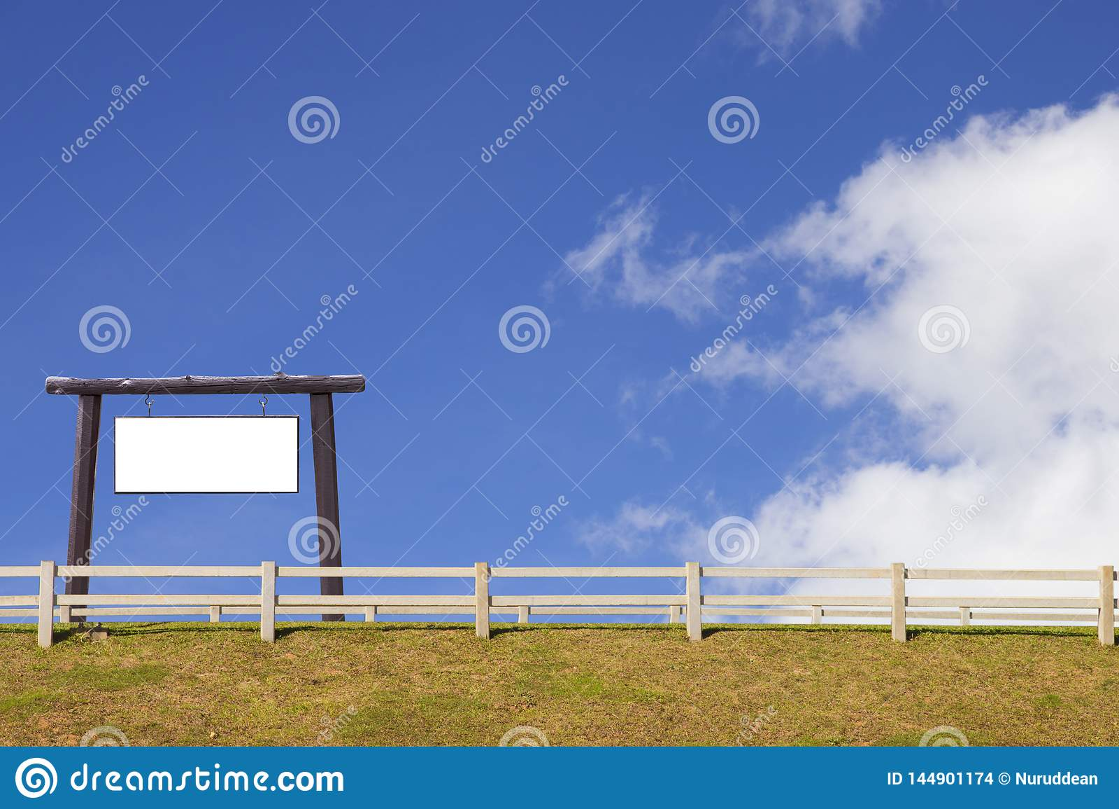 Enseigne et barrière en bois avec l herbe et le ciel bleu