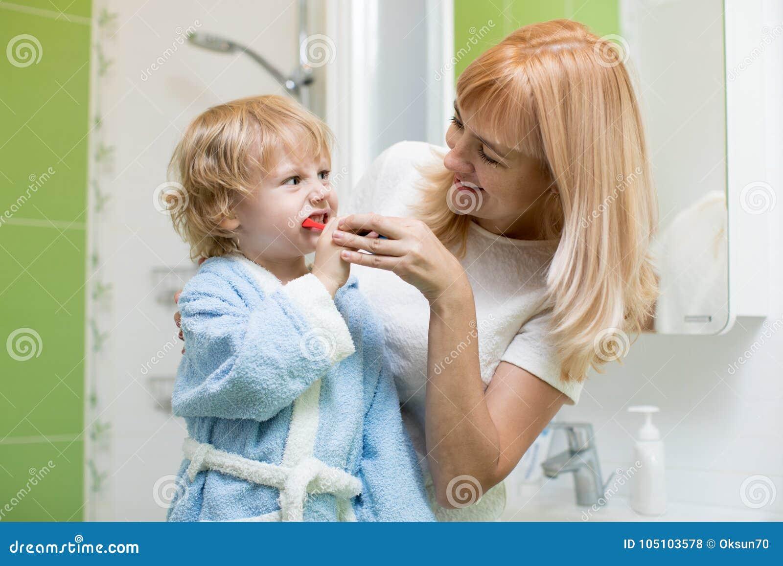 Ensino da mãe e filho de ajuda da criança como escovar seus dentes