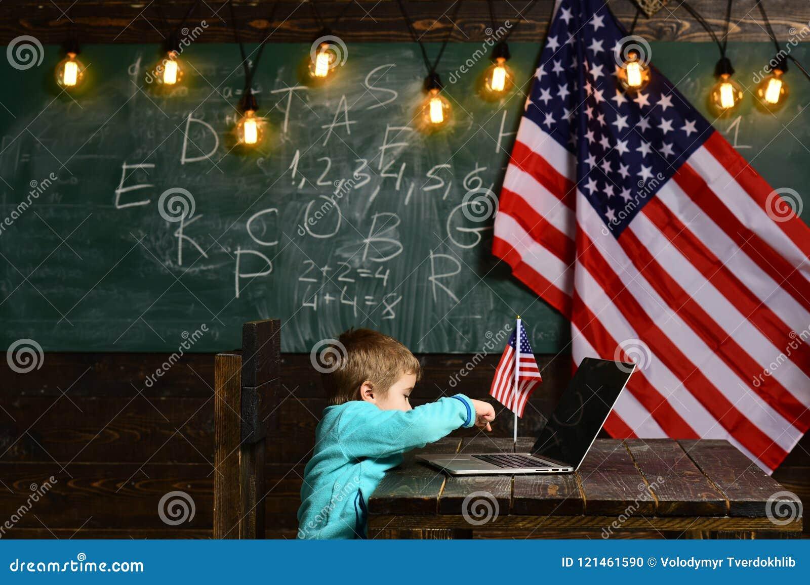 Ensino eletrónico ou cursos em linha em casa que educam Rapaz pequeno com o portátil para o negócio na bandeira americana Patriot