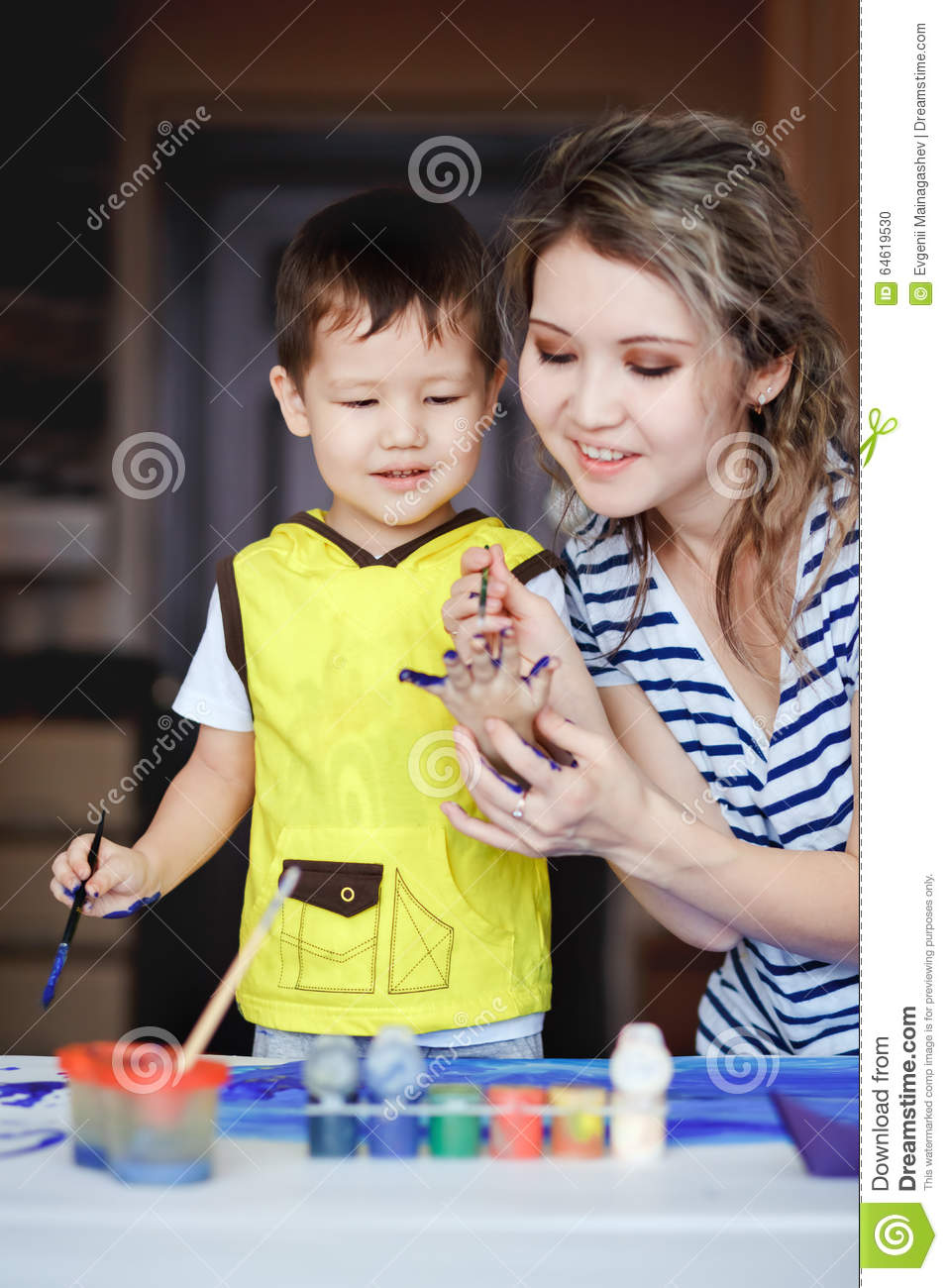 Entertaining childhood, a little boy playing with his mother, draws, paints on the palms.