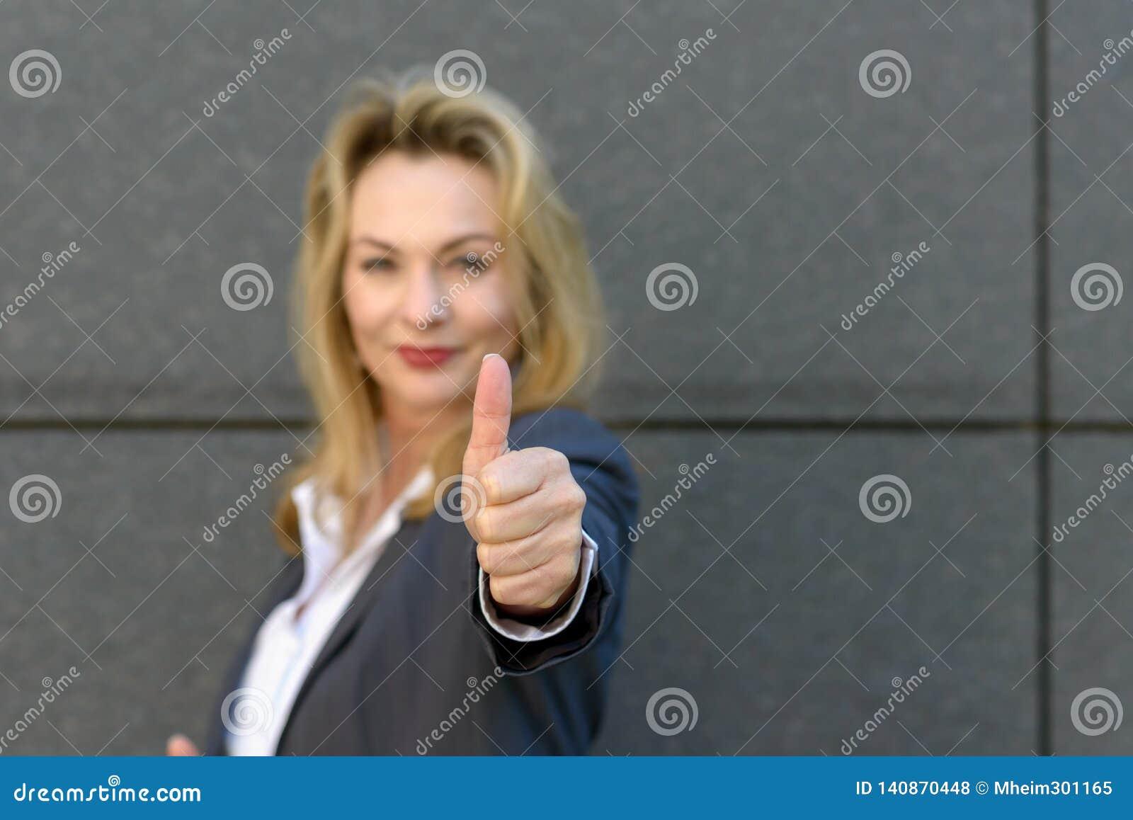 Enthousiaste gemotiveerde vrouw die een duim opgeven