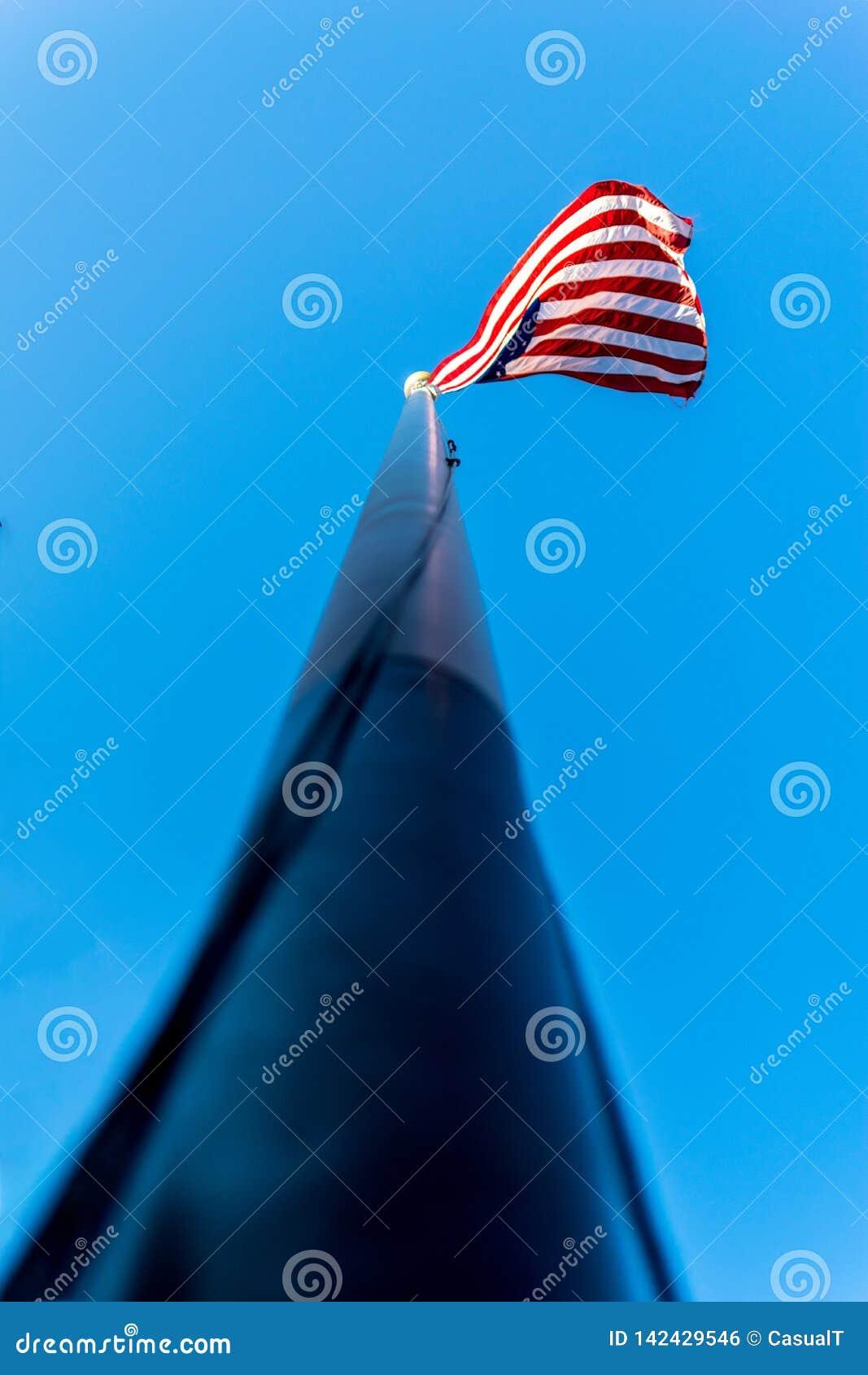 Entlang einem Fahnenmast, in Richtung der amerikanischen Flagge, der Sterne u. der Streifen oben blicken, bewegend in den Wind, g