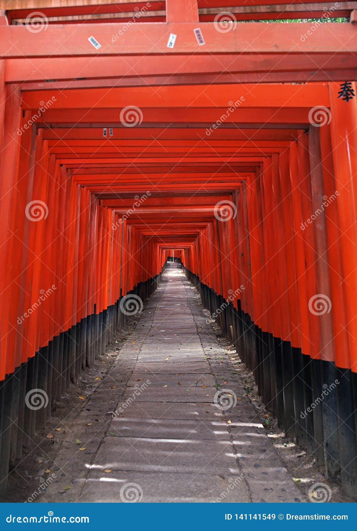 Entrée japonaise de tombeau avec les colonnes rouges et le fond noir de toits