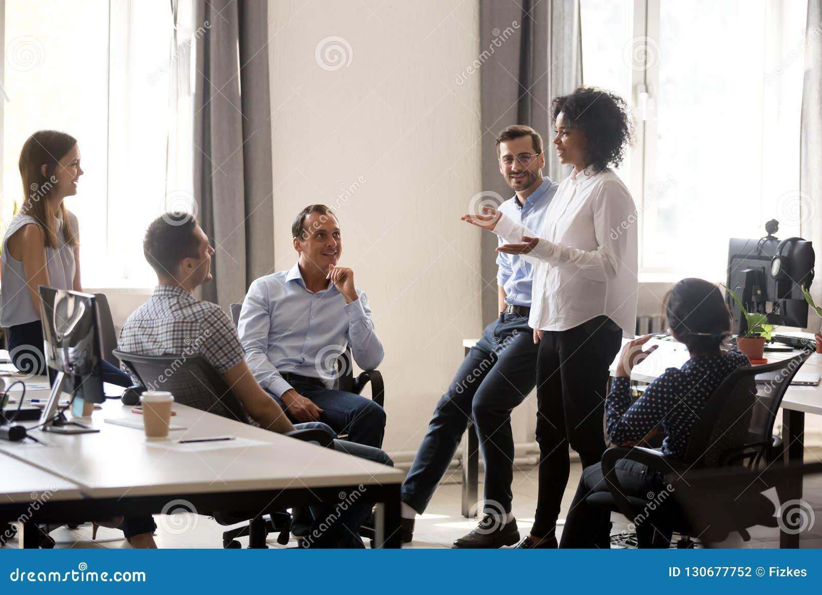 Entraîneur africain de sourire parlant au meetin divers de groupe de sociétés